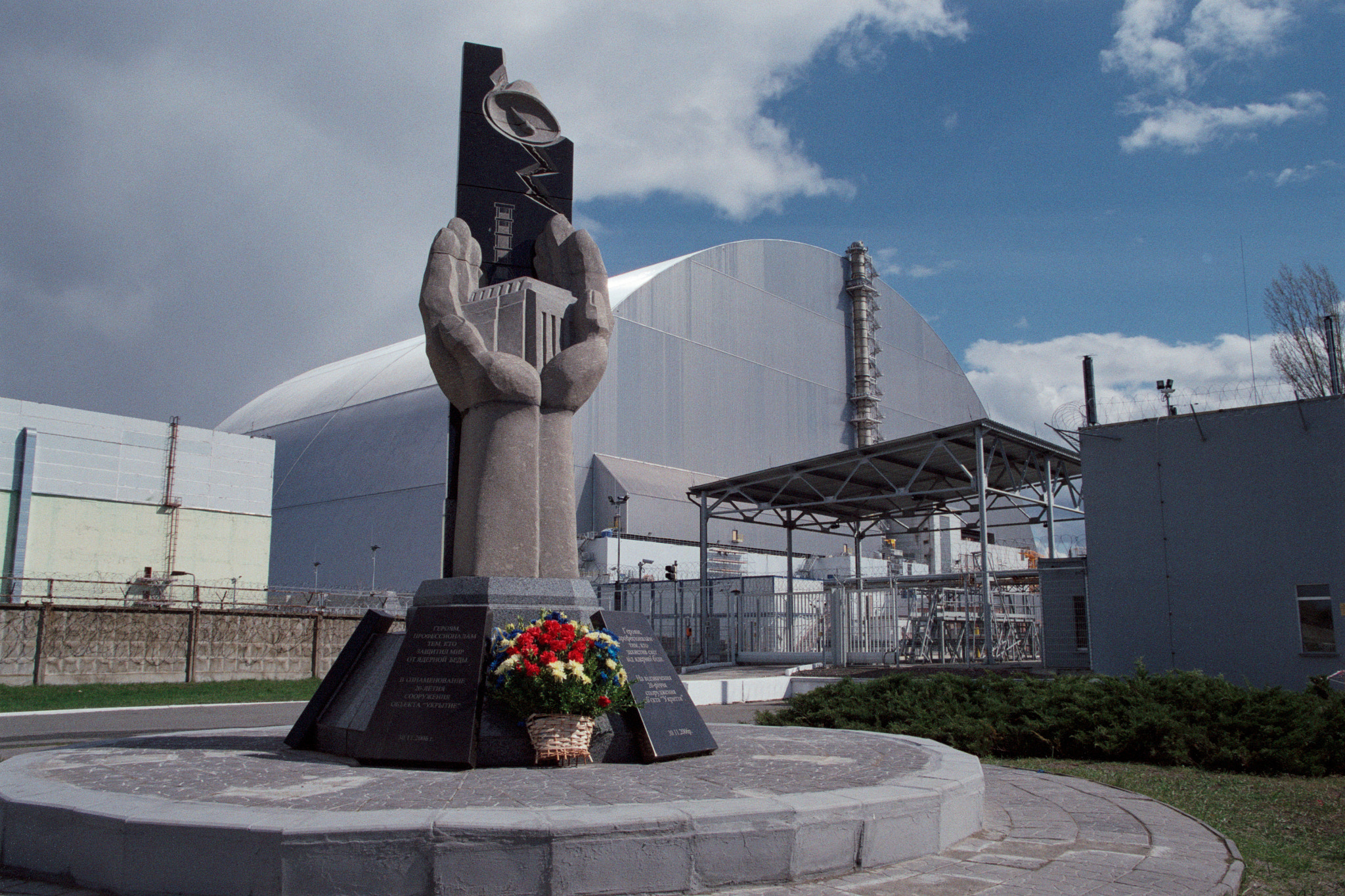 Protective confinement over the fourth power unit of the Chernobyl nuclear power plant. In front, a monument to the heroes who sealed the reactor at the cost of incredible efforts. Picture by Stanislav Nepochatov. CC BY-SA 3.0