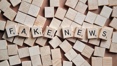 Fitxes de scrabble del revés esteses sobre una superfícies. Només n'hi ha vuit de cara amunt on es pot llegit la paraula fake news.